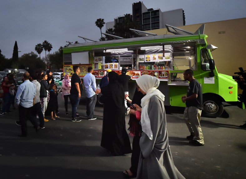 Church members from the Islamic Center of Santa Ana lineup after sunset in front of a taco truck, part of Taco Trucks at Every Mosque, during an iftar meal, one of the religious observances of Ramadan as they gathering to break their fast together. Steven Georges, Contributing Photographer